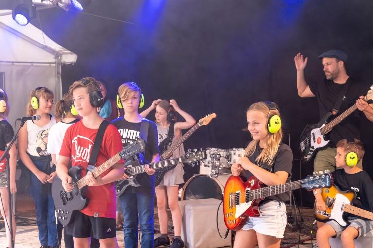 Kinder auf der Bühne mit Gitarren und Mikrofonen. Ein erwachsener Leiter steht hinten rechts